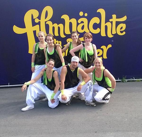"""Gruppenfoto Tanzverein Empire of Outcast in Lost-Kostümen vor dem Plakat """"Filmnächte am Elbufer"""""""