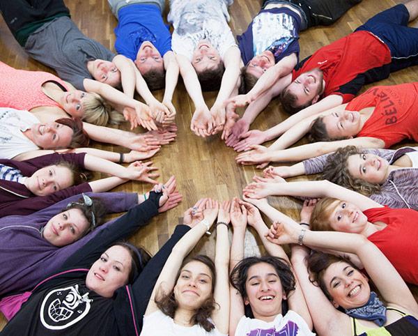 Tänzerinnen bilden liegend auf dem Rücken einen Kreis, Arme nach oben