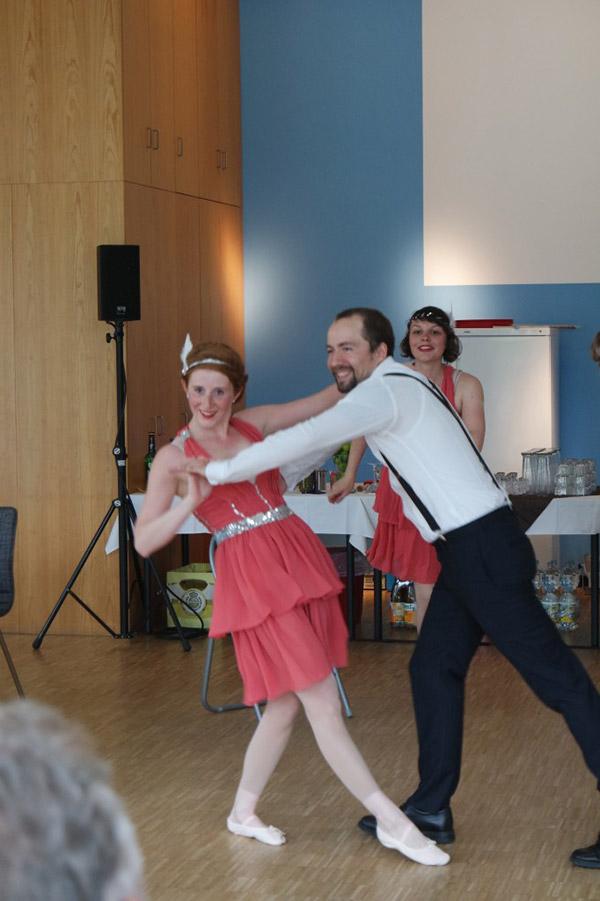 Tänzerin in rosa Kleid und Tänzer mit Hosenträger tanzen zusammen