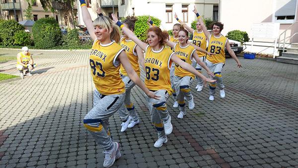 Tänzer bilden eine Reihe, tanzend zum Publikum, Hip Hop Auftritt im Freien, Tanzverein Empire of Outcast