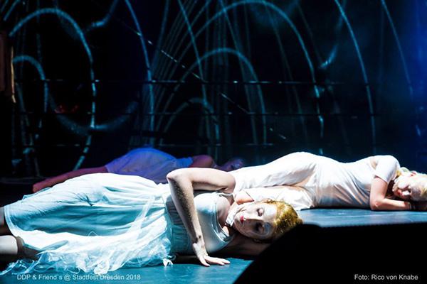 Trainerin Anne-Katrin, weißes Kleid, liegend beim Auftritt der Black and White Show auf der Bühne