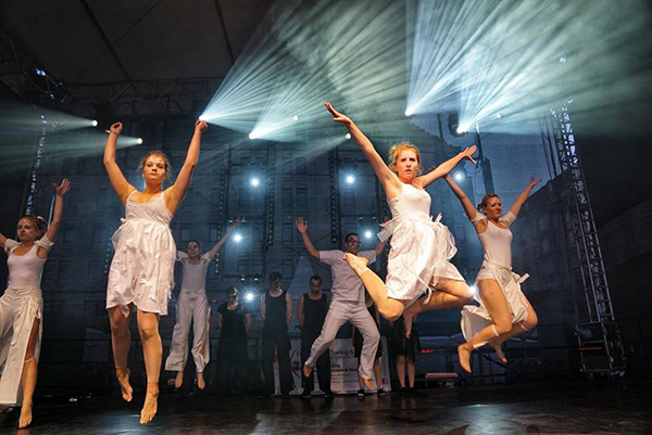 Tanzauftritt auf der Bühne des Dresdner Stadtfestes des Tanzvereins Empire of Outcast, TänzerInnen springend in weißen Kostümen