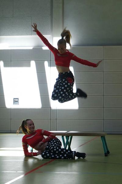 zwei Tänzerinnen in rot und schwarz, springend, während des Tanzfestivals the royal knights