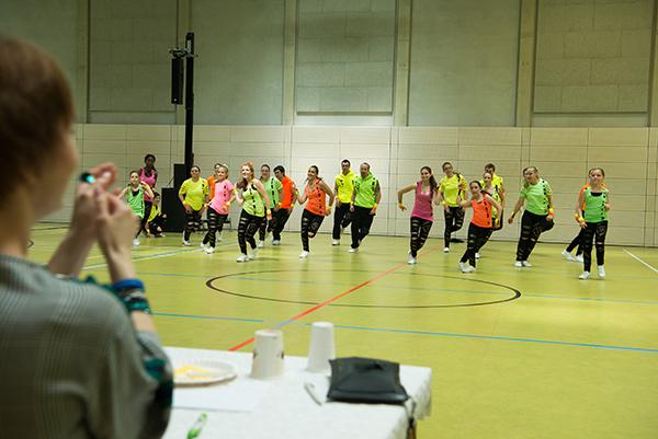 Während des Auftritts der Show Old to New, Tanzmiglieder in neonfarbenen Kostümen