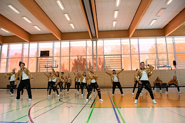 Tanzmitglieder des Tanzvereins präsentieren die Premiere der Jubiläumsshow in goldenen Kostümen