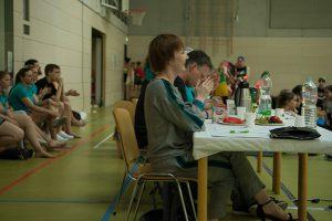 Jurymitglieder am Jurytisch, beobachten Tanzgruppen