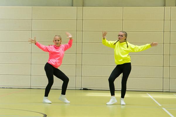 Zwei Tänzerinnen tanzen Duett, in neongelb und rosa