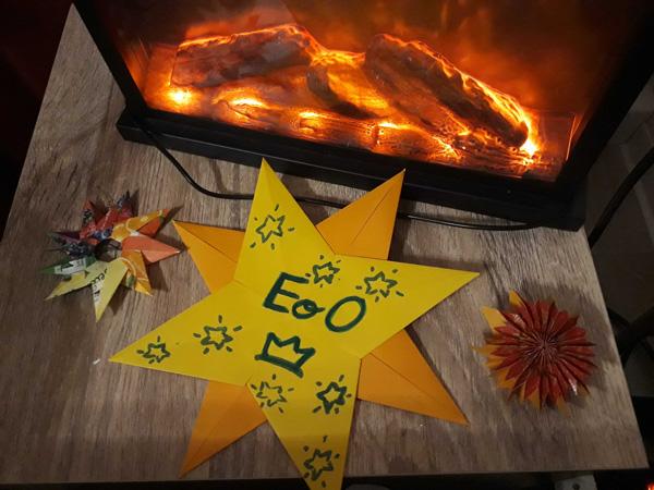 Gelber Papierstern mit dem Empire-Logo, auf einem Tisch vor einem Kaminfeuer